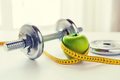 close up of dumbbell and apple with measuring tape