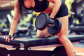 woman flexing muscles with dumbbell in gym