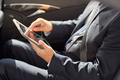 senior businessman with tablet pc driving in car