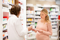 happy pregnant woman and apothecary at pharmacy
