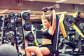 young woman flexing muscles with dumbbell in gym