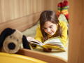 Young Girl Laying Down Reading Book On Bed