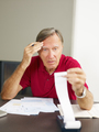 Senior Man Checking Home Finances And Bills With Worried Expression