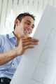 Male Architect Looking At Blueprints And Building Plans In Office