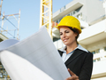 Female Engineer With Yellow Helmet Looking At Building Plans In Construction Site