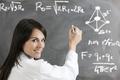 Portrait Of Female Scientist Writing Formula On Blackboard