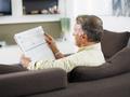 Senior Man Reading Newspaper On Sofa At Home