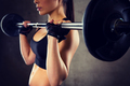 close up of woman holding barbell in gym