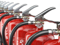 Row of fire extinguishers isolated on white background.