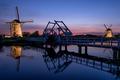 Windmills and a bridge illuminated at dusk