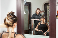 Woman looking in the mirror while getting a new hairstyle