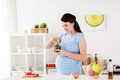 pregnant woman eating pickles at home kitchen