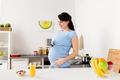 happy pregnant woman with cup at home kitchen