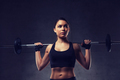 young woman flexing muscles with barbell in gym