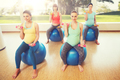 happy pregnant women exercising on fitball in gym