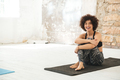 Happy young woman sitting in yoga studio