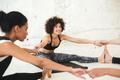 Happy multiethnic people in yoga studio stretching.