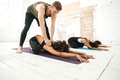 Male yoga instructor helping woman to stretch