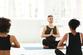 Group of women with male instructor sitting on yoga mats
