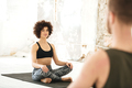Smiling young woman having a yoga class with male instructor