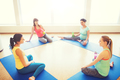 happy pregnant women sitting on mats in gym