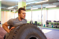 man doing strongman tire flip training in gym