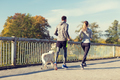 couple with dog running outdoors