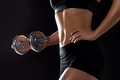 close up of sporty woman exercising with dumbbell