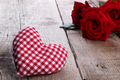 Red roses and a heart on wooden background