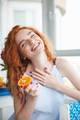 Cute cheerful young redhead lady holding orange. Eyes closed.