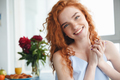 Cheerful young redhead lady sitting near flowers