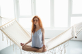 Concentrated young redhead lady sitting on hammock meditate