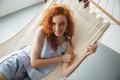 Cute cheerful young redhead lady lies on hammock