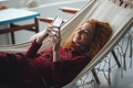 Beautiful happy young redhead lady lies on hammock and chatting