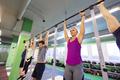 group of people hanging at horizontal bar in gym