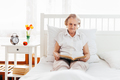 Elderly woman sitting comfortably in bed reading her favourite book