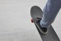 Skater and skateboard leg detail. Lifestyle urban background. Outdoors