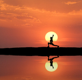 Silhouette of a standing sporty woman practicing yoga