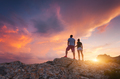 Silhouette of happy people on the mountain against colorful sky
