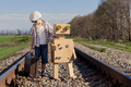 Happy little boy and robot walking with suitcase on the railway