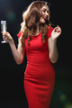 Cheerful attractive woman in red dress dancing and drinking champagne