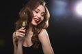 Cheerful gorgeous woman with glass of champagne standing and smiling