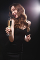 Cheerful attractive young woman drinking champagne and having fun