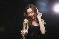 Happy charming young woman drinking champagne and dancing