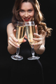 Smiling attractive young woman holding two glasses of champagne