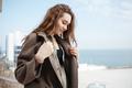 Woman unbutonning her coat