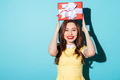 Portrait of an excited girl in dress holding present box