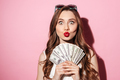 Funny young brunette woman holding money
