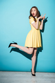 Brunette woman in yellow dress pointing