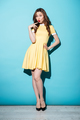 Pretty young brunette woman in yellow dress